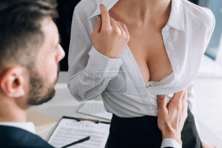 Photo pour Vue recadrée de l'homme d'affaires étreignant secrétaire sexy avec gros seins au bureau - image libre de droit