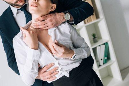 Photo pour Crochet vue d'homme d'affaires en costume serrant sexy secrétaire avec grosse poitrine dans le bureau - image libre de droit