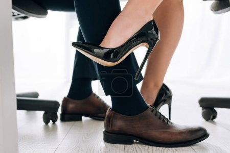 Photo for Cropped view of secretary in heels touching leg of businessman in office - Royalty Free Image