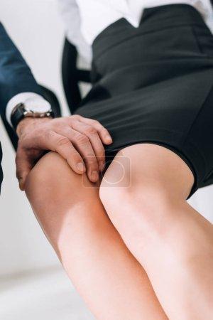 Photo pour Vue recadrée de l'homme d'affaires toucher jambe du secrétaire en fonction - image libre de droit