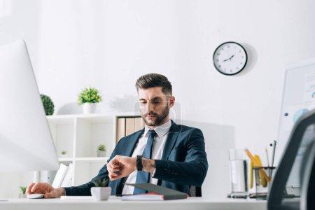 Foto de Hombre de negocios sentado en la mesa y mirando el reloj de pulsera en la oficina - Imagen libre de derechos