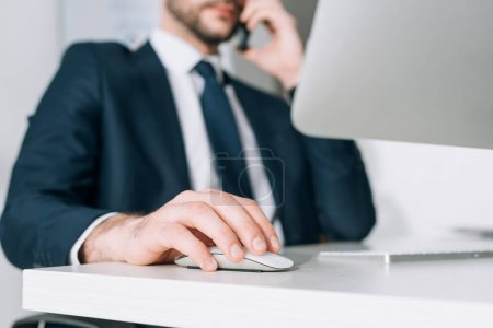cropped view of businessman in suit sitting at table and talking  on smartphone