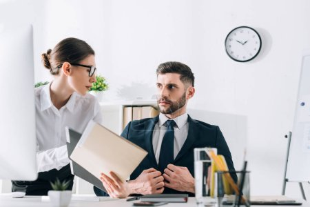 attractive secretary showing folder to handsome businessman in office