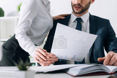 Photo pour Vue recadrée du secrétaire avec gros sein toucher la main de l'homme d'affaires au bureau - image libre de droit