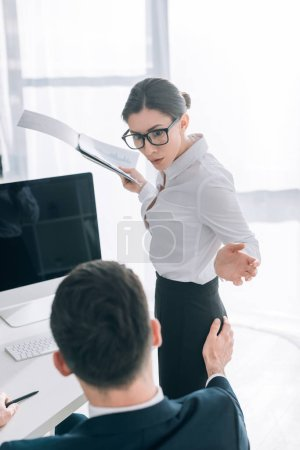 selective focus of businessman touching butt of shocked secretary with folder in office