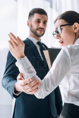 Photo pour Foyer sélectif de l'homme d'affaires toucher la main du secrétaire choqué dans le bureau - image libre de droit