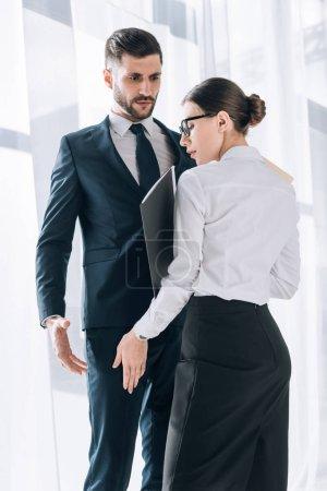 attraktive Sekretärin berührt Bein eines schockierten Geschäftsmannes im Amt
