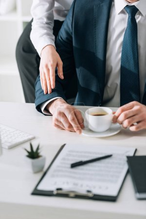Photo for Cropped view of secretary touching hand of businessman in office - Royalty Free Image