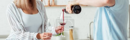 Photo for Panoramic shot of man pouring red wine in glass near girl - Royalty Free Image