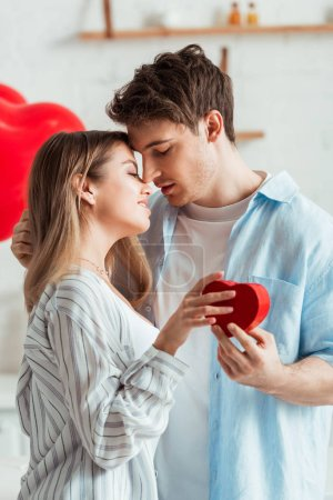 side view of man holding heart-shaped gift box near beautiful girl