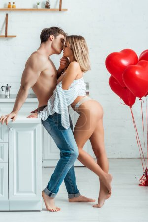Photo for Hot couple kissing near red heart-shaped balloons - Royalty Free Image