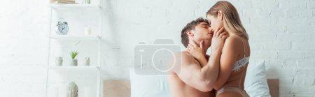 Photo pour Photo panoramique d'une femme passionnée en sous-vêtements en dentelle baisant beau copain en chambre - image libre de droit