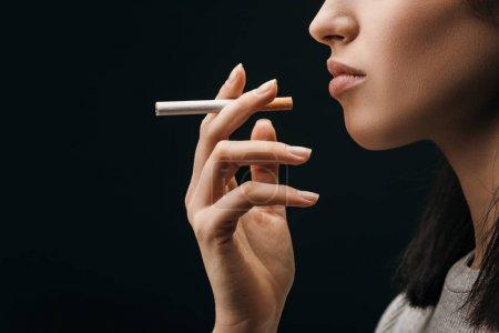 Photo pour Vue latérale de la femme tenant la cigarette isolée sur noir - image libre de droit