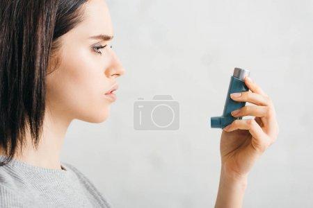 Photo pour Vue latérale de la jeune femme tenant inhalateur sur fond blanc - image libre de droit