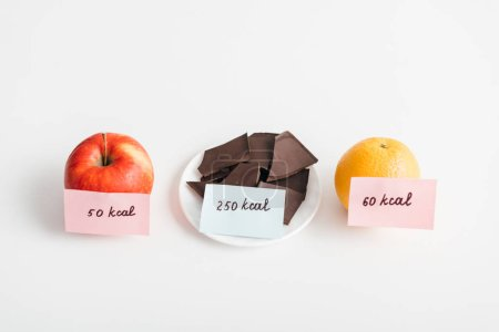 Fresh apple, orange and chocolate with calories on cards on white background, calorie counting diet