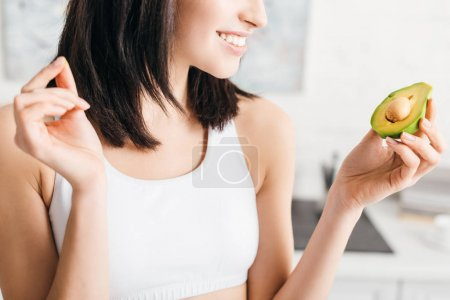 Photo for Cropped view of smiling sportswoman holding piece of avocado in kitchen - Royalty Free Image