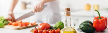 Photo for Selective focus of olive oil and fresh vegetables near woman cooking salad on kitchen table, panoramic shot - Royalty Free Image