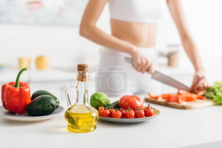 Photo for Selective focus of organic vegetables and avocado near sportswoman cooking salad on kitchen table - Royalty Free Image