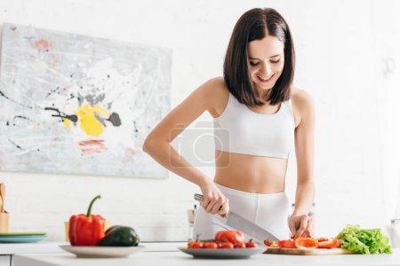 Photo pour Sportive souriante coupant légumes frais et laitue sur la table de cuisine - image libre de droit