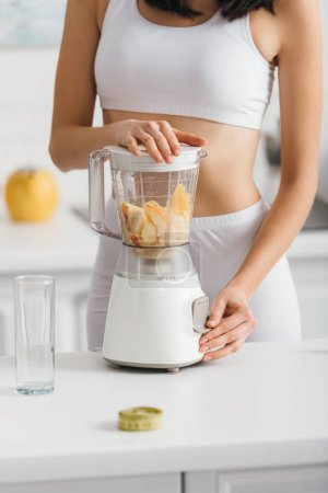 Photo for Cropped view of fit sportswoman preparing smoothie with fresh fruits near measuring tape on kitchen table - Royalty Free Image