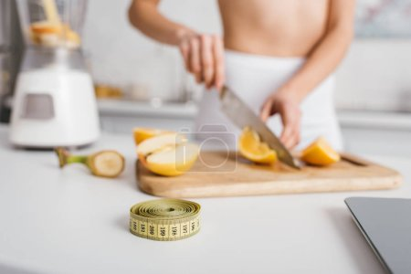 Photo for Selective focus of measuring tape and scales near fit girl cutting fresh vegetables for smoothie on kitchen table, calorie counting diet - Royalty Free Image
