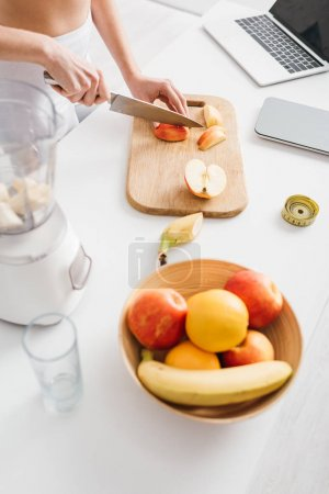 Photo for High angle view of woman cutting fruits for smoothie with measuring tape, scales and laptop on kitchen table, calorie counting diet - Royalty Free Image