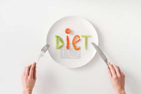 Top view of woman with cutlery and diet lettering from vegetable slices on plate on white background
