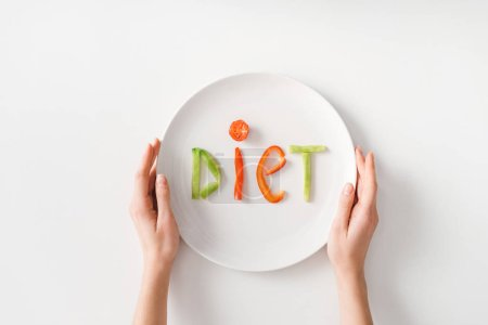 Top view of woman holding plate with diet lettering from vegetable slices on white background