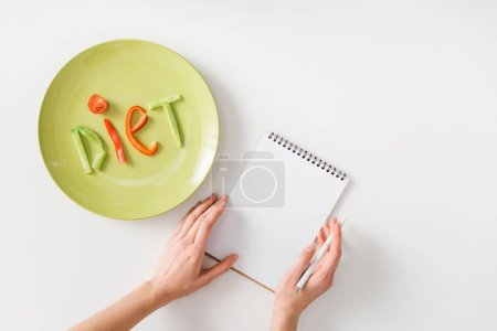 Photo for Top view of woman with pen and notebook near plate with diet lettering from vegetable slices on white background - Royalty Free Image