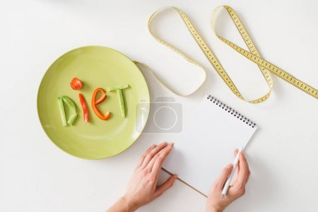 Photo pour Top view of woman writing in notebook near measuring tape and plate with diet lettering from vegetable slices on white background - image libre de droit