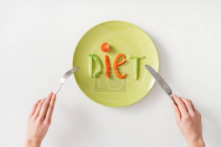 Top view of woman with cutlery near word diet from vegetable slices on plate on white background