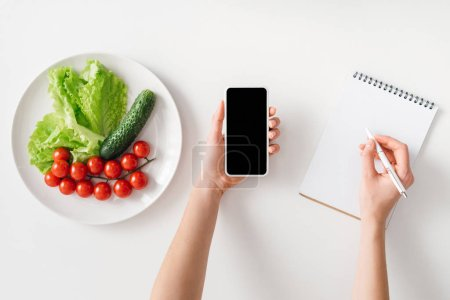 Top view of woman holding smartphone and writing in notebook near ripe vegetables on plate on white background