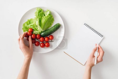 Photo for Top view of woman holding pen near notebook and fresh vegetables on plate on white background - Royalty Free Image