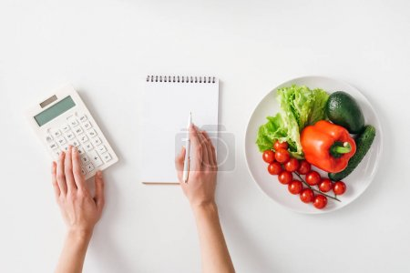 Top view of woman using calculator near notebook and fresh vegetables on plate on white background