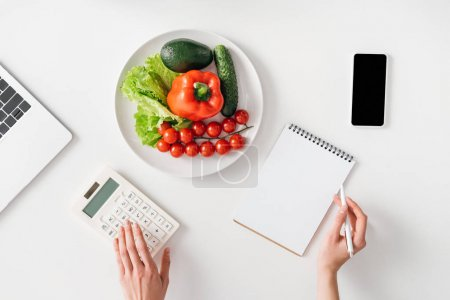 Top view of woman using calculator near digital devices, notebook and fresh vegetables on white background