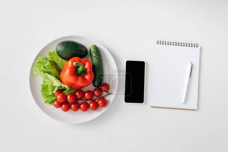 Photo for Top view of vegetables and avocado on plate, smartphone and notebook on white background - Royalty Free Image
