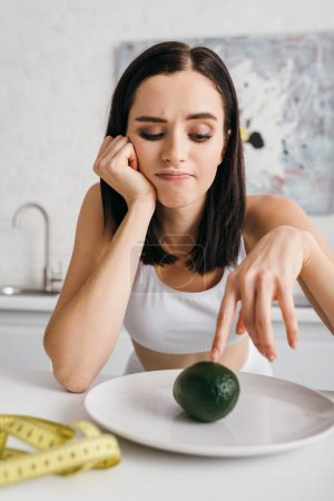 Selective focus of thoughtful sportswoman looking at avocado near measuring tape on kitchen table