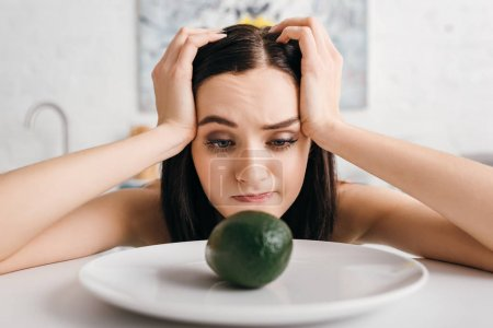 Attractive pensive woman with hands near head looking at avocado on kitchen table