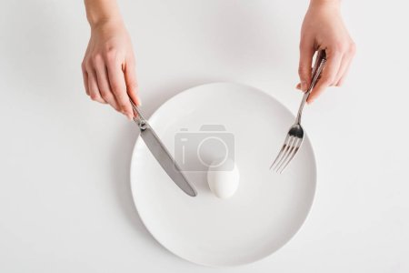 Photo for Top view of woman holding cutlery near egg on plate on white background - Royalty Free Image
