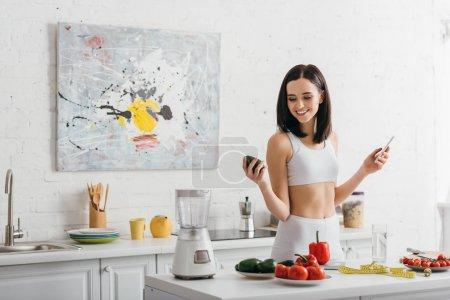 Lächelnde Sportlerin mit Avocado und Smartphone neben Gemüse und Maßband auf dem Tisch, Kalorienzähler-Diät