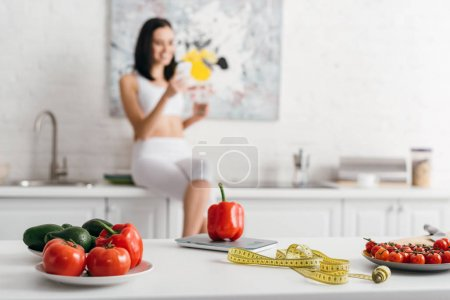 Photo for Selective focus of fresh vegetables with measuring tape near scales and sportswoman with smartphone and glass of water in kitchen, calorie counting diet - Royalty Free Image