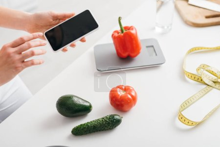 Cropped view of girl holding smartphone with blank screen near vegetables, scales and measuring tape on kitchen table, calorie counting diet