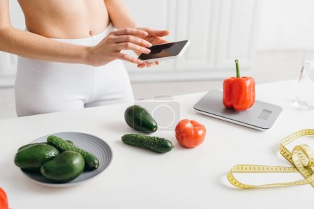 Photo for Cropped view of fit girl using smartphone near vegetables, measuring tape and scales on table, calorie counting diet - Royalty Free Image