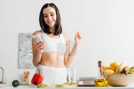 Photo for Low angle view of smiling sportswoman using smartphone near fruits, vegetables and measuring tape in kitchen - Royalty Free Image
