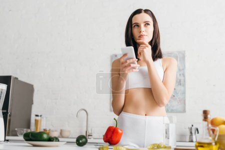 Pensive sportswoman using smartphone near fresh vegetables, fruits and measuring tape on table