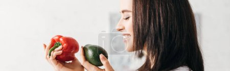 Photo for Side view of smiling girl holding bell pepper and avocado, panoramic shot - Royalty Free Image