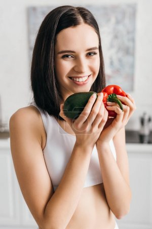 Photo for Beautiful sportswoman holding avocado and bell pepper and smiling at camera in kitchen - Royalty Free Image