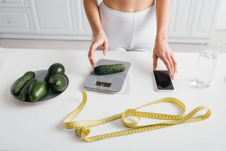 Photo pour Cropped view of slim woman putting cucumber on scales near smartphone and measuring tape on kitchen table, calorie counting diet - image libre de droit