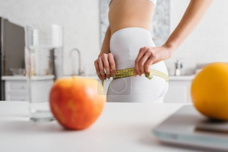 Photo pour Selective focus of slim girl measuring hips near fruits, glass of water and scales on table in kitchen, calorie counting diet - image libre de droit