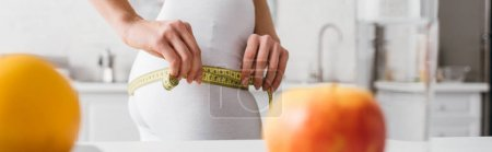 Photo for Panoramic shot of fit woman measuring hips near fresh fruits on kitchen table - Royalty Free Image